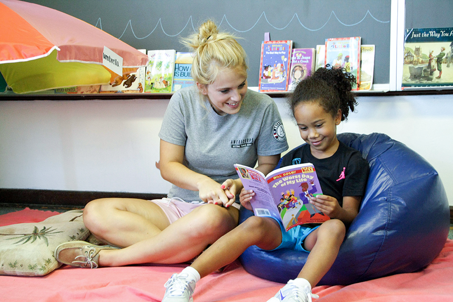 Energy Express mentor reading to young girl
