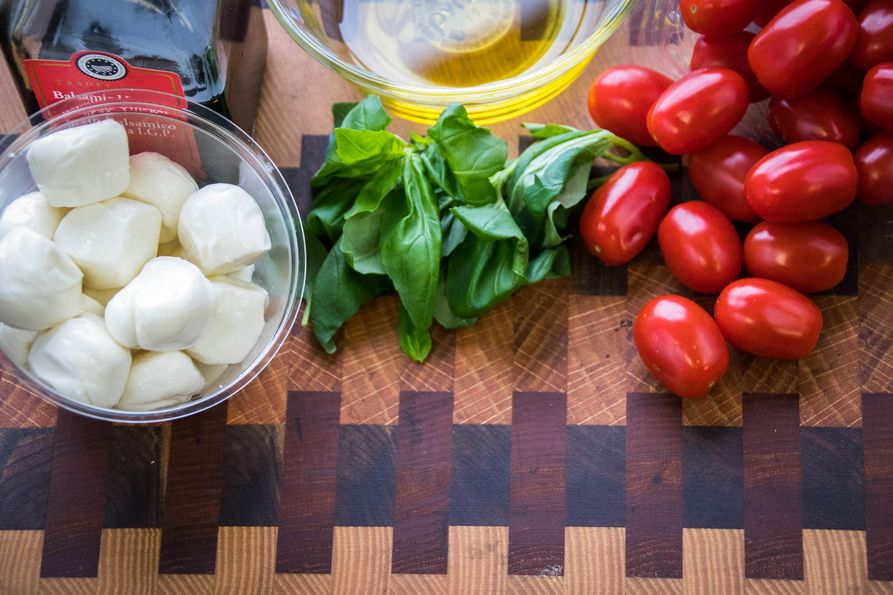 Ingredients for caprese salad kabobs on cutting board