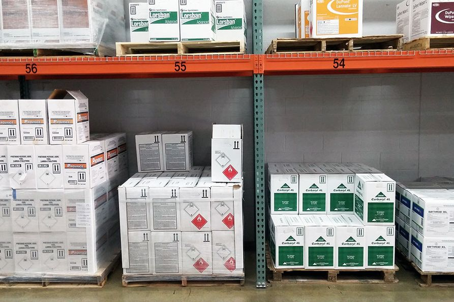 Rows of boxes of pesticides sit on shelves.