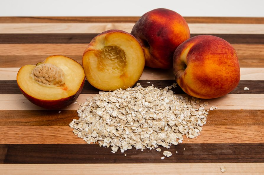 Peaches and oats on a wooden cutting board.