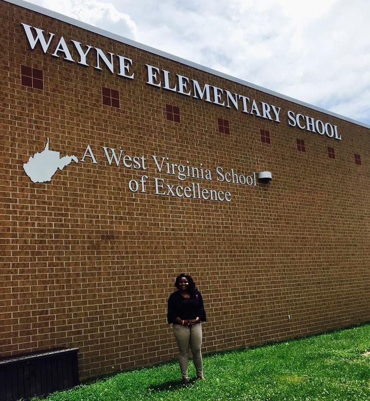 2018 CEOS International Student Line-Audrey stands in front of Wayne Elementary School building