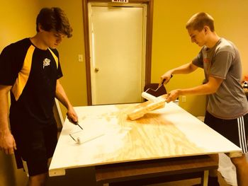 two teen boys paint the foundation color onto plywood