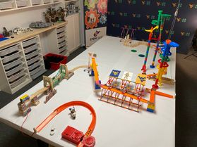Rube Goldberg Machine which uses toys, cars, marbles and legos to make a chain reaction of events leading.