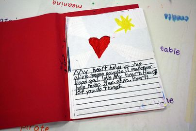 child's journal entry with art of heart and sun above writing