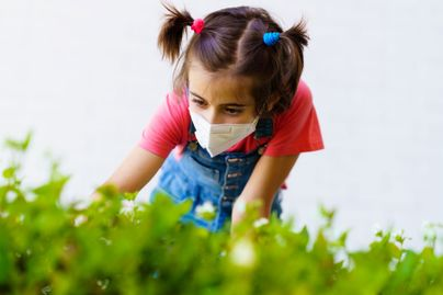 A girl wears a protective mask while picking fruit.