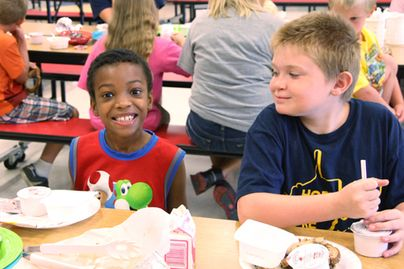 two boys eating lunch in school cafeteria