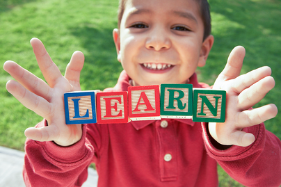 "young boy holding blocks with letters on them spelling out the word ""learn"""