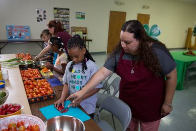 Kids cutting tomatoes in a kitchen with help from adult