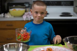 Boy in kitchen with a measuring cup of tomatoes, bowls, cutting board, and knife