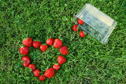 strawberries dumped out of container into grass, forming a heart