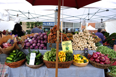 farmers market stand with baskets of vegetables