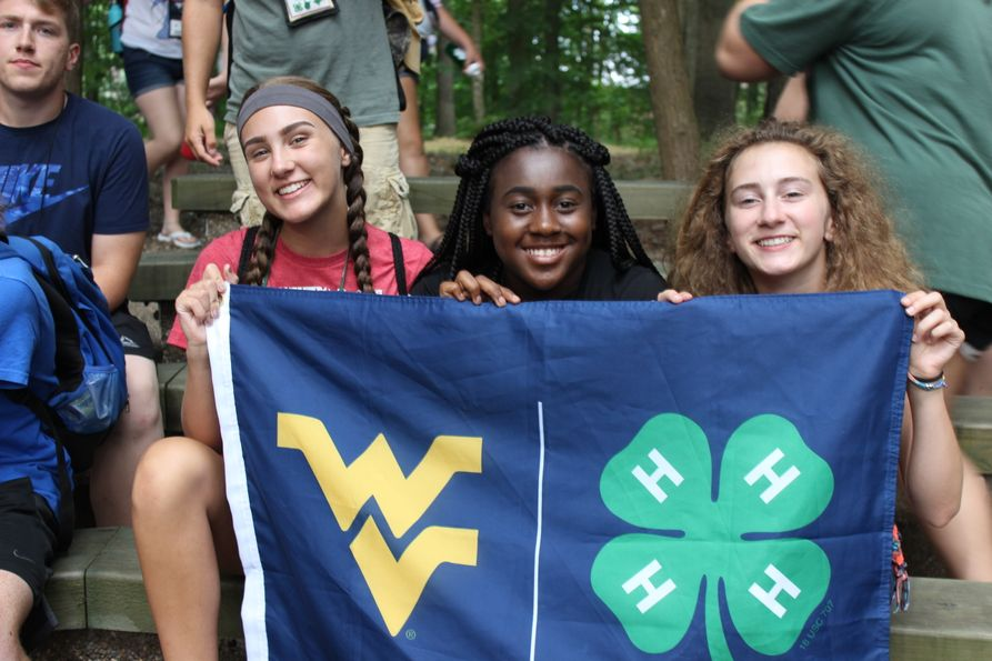 Three girls at 4-H Council Circle holding a flag with the WVU Flying WV and 4-H clover on it.