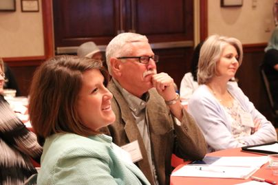 Three Community Leadership Academy participants listen to a speaker.