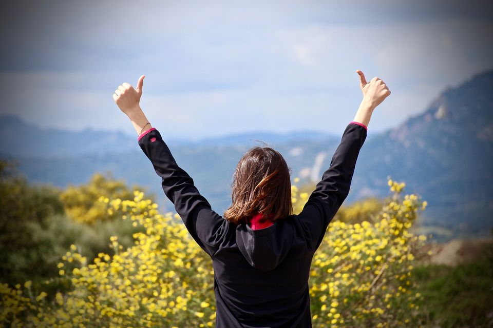 A young woman stands proudly with her arms outstretched.