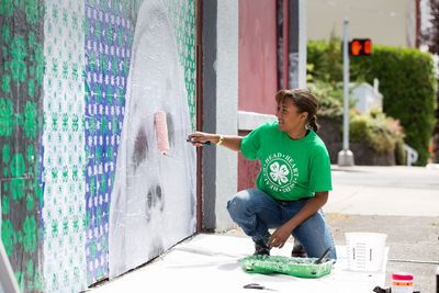 Teenager painting a mural