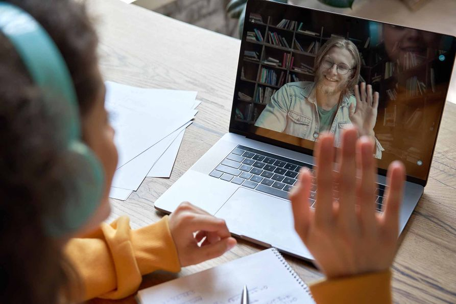A teen girl waves to a male friend on her laptop using conferencing software.