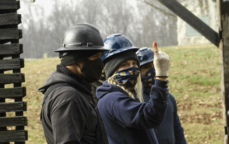 Two people wearing hard hats and face masks discuss a building structure