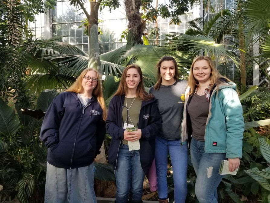 Four youth 4-H girls stand on an overlook at the U.S. botanical gardens surrounded by diverse plant life.