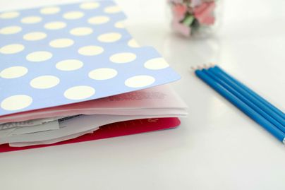 A stack of papers in a folder on a desk with three pencils and a vase of flowers.