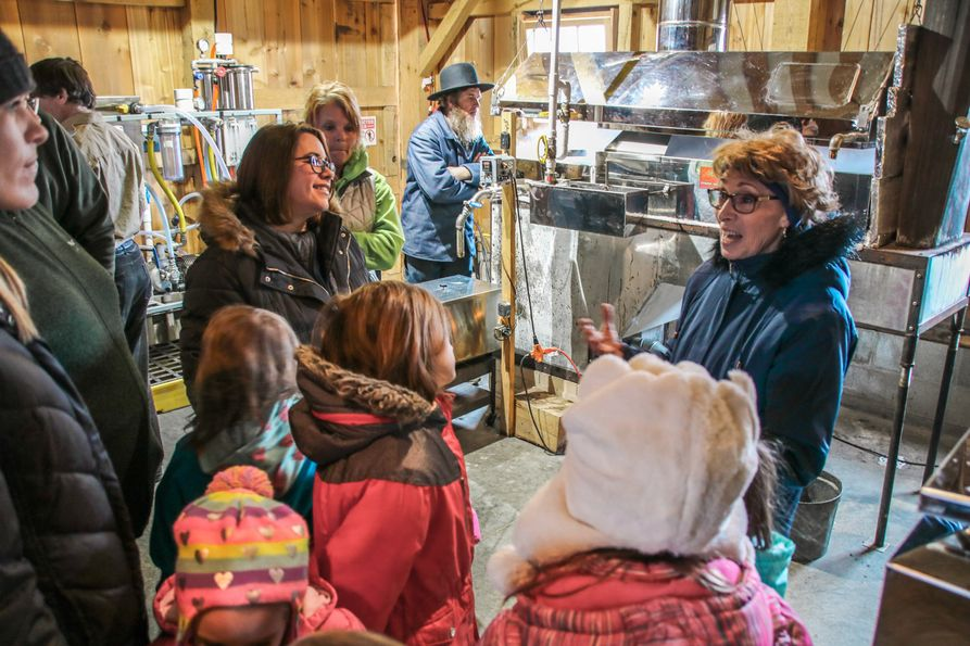 Group of youth and adult visitors gather around tour guide during an agritourism experience at Family Roots Farm.