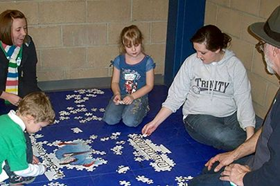 A group of adults and youth work to complete puzzles as part of a STEM activity