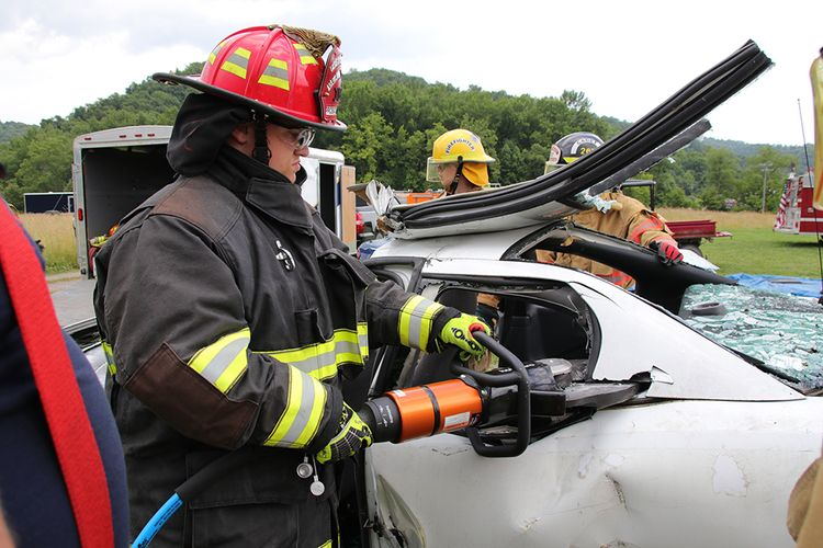 Jr Firefighter in gear uses tools to disassemble a car for a rescue