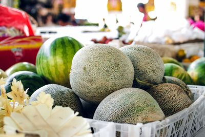 cantaloupes and watermellons stacked at a farmers market