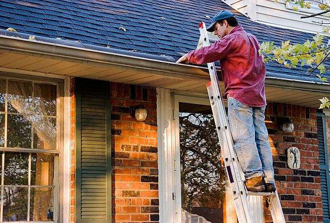 man on ladder cleaning house gutters