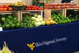 Assorted vegetables arranged market-style on table with WVU tablecloth