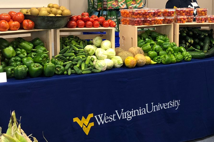 Photos of assorted vegetables on a table with WVU tablecloth