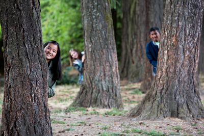 Three teens peaking out from behinds trees