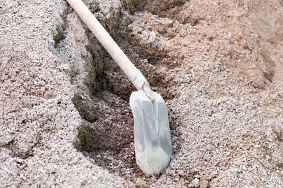 A shovel rests on the ground in a dirt trough.