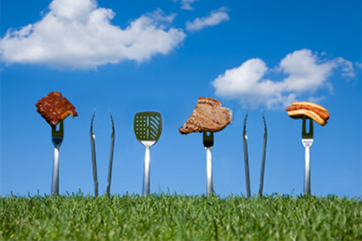 fun photo of bbq instruments standing vertically in grass with blue sky behind, some items have food on them