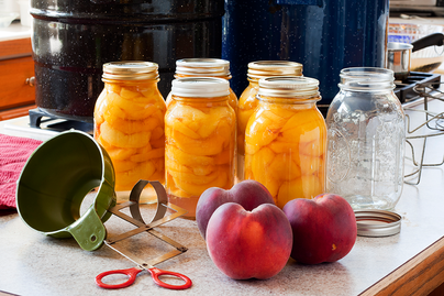 peaches, canning equipment, and jars of canned peaches