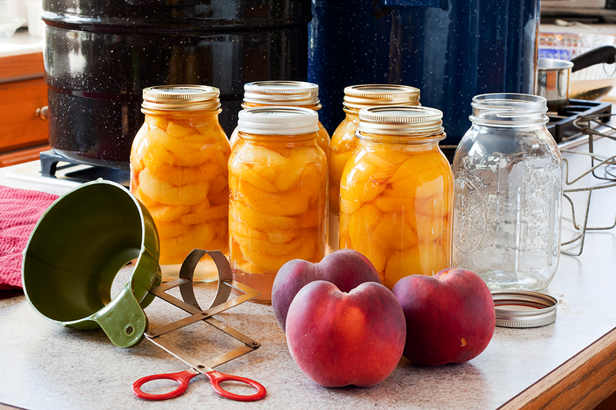 canning tools and 5 jars of canned peaches on a countertop