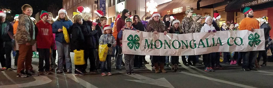 4-H members line up and prepare to walk in the parade holding a 4-H banner.