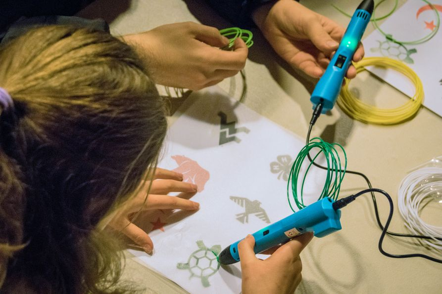Students use 3-D printing pens to create symbols