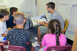 young man reading to a small group of children as he points to the illustrations