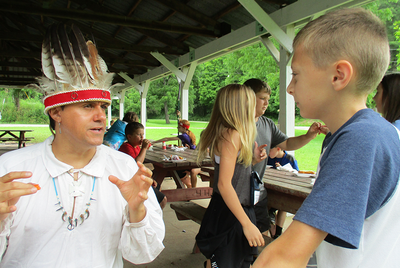 Young camper talking to Native American cultural expert in traditional headdress