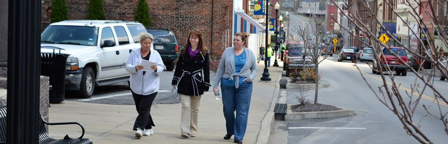 West Virginia University Extension Service Community Development educators walking down a community sidewalk and conducting a walkability study.