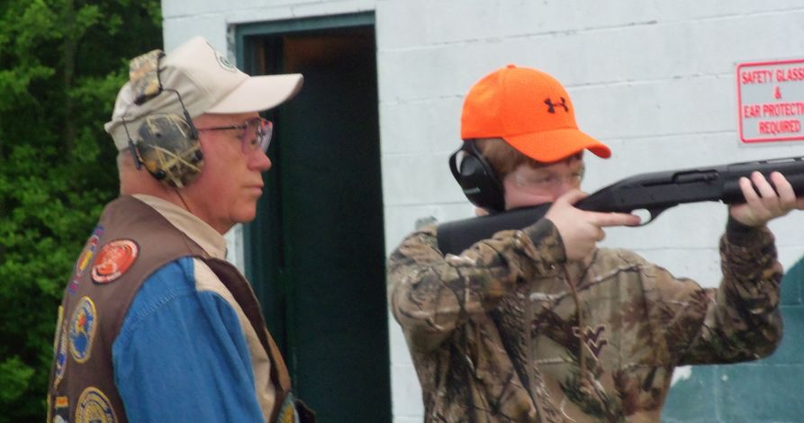 Coach looks on as young as 4-H member holds and aims a shotgun.