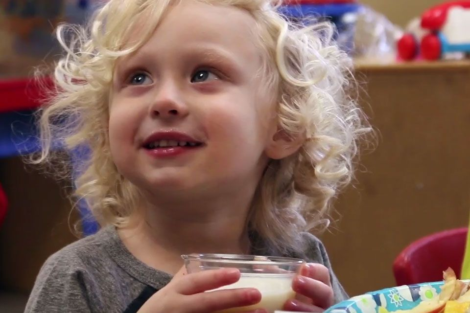 A smiling child holds a cup of milk.