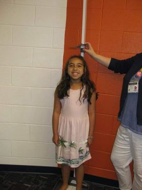 An elementary school student has her height measured as part of a CARDIAC screening.