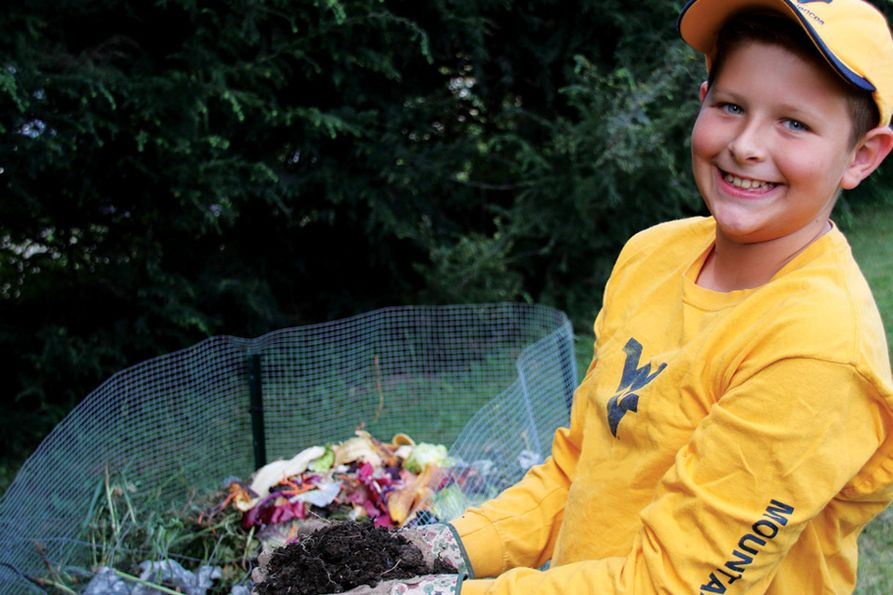 The cover of WVU Extension's 2019 Garden Calendar features a boy in Mountaineer gear wearing gloves and holding fresh compost. The cover reads Back to Garden Basics.