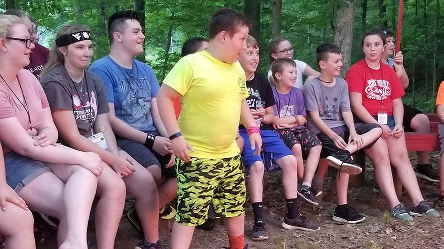 Young male child in a yellow shirt stands up to tell a story surrounded by fellow 4-H'ers.