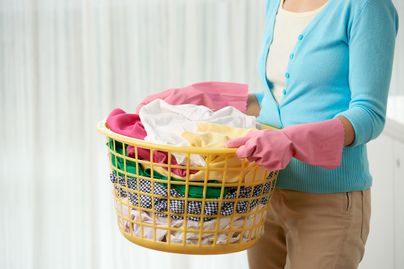 woman wearing pink gloves holding laundry basket full of clothes