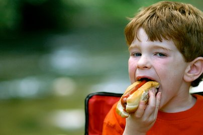 red haired boy eating a hot dog