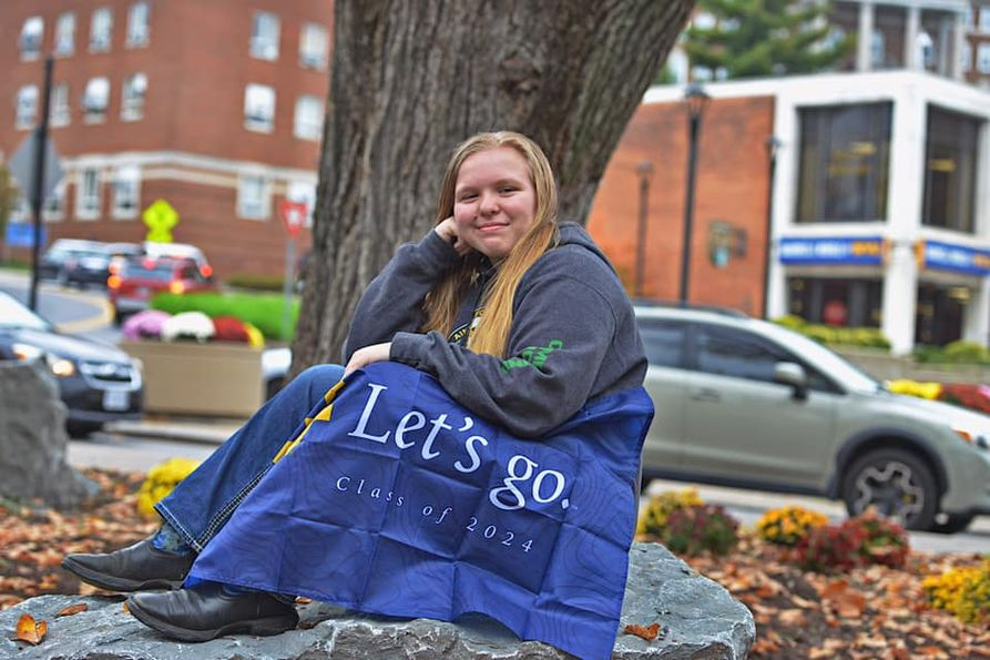 4-H'er Jamie Yoder sits in front of a tree with a Mountaineer flag.