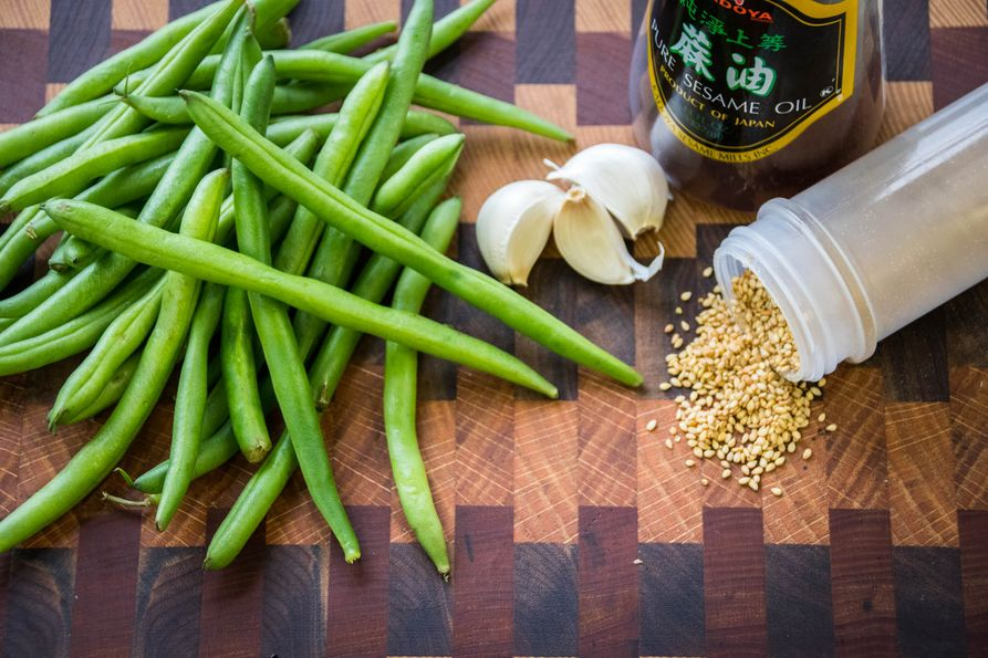 Ingredients for garlic-sesame green beans on cutting board