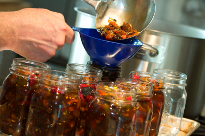pouring food into glass jars to prepare for canning